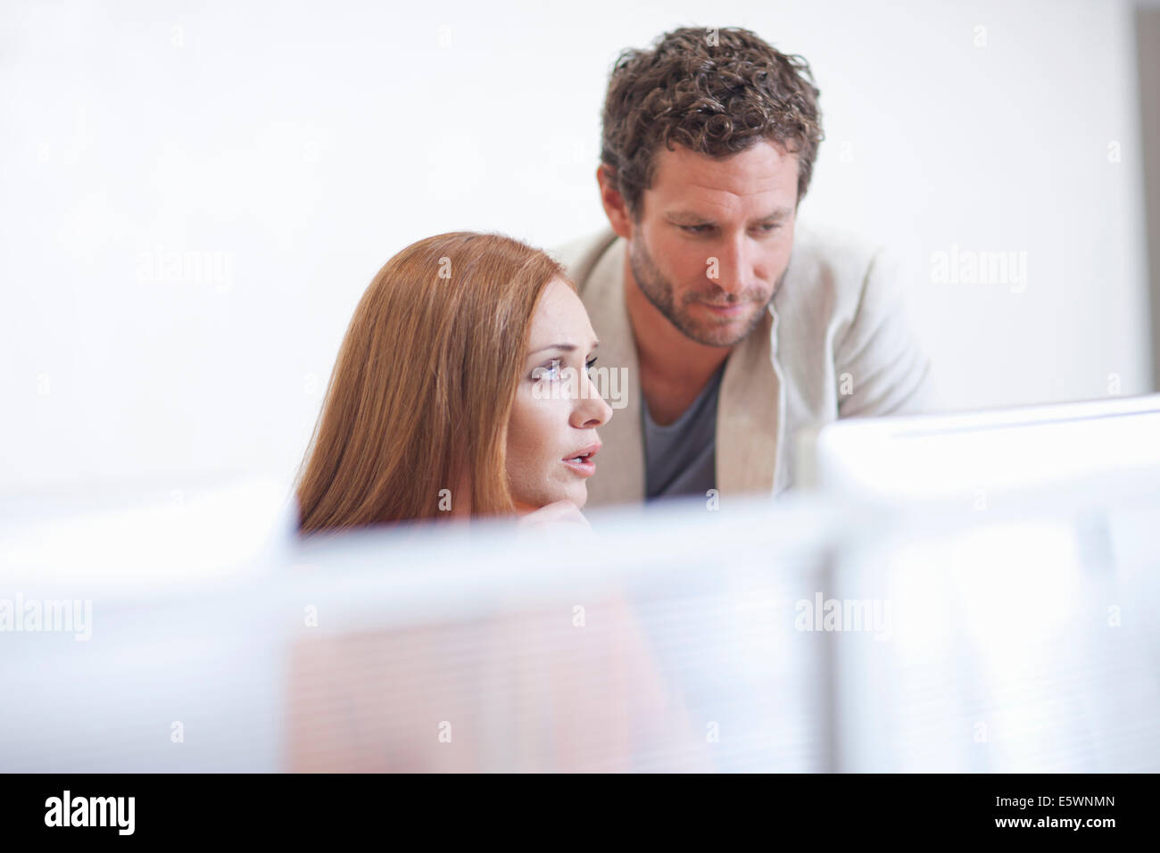 Female office worker with colleague, looking worried - Stock Image