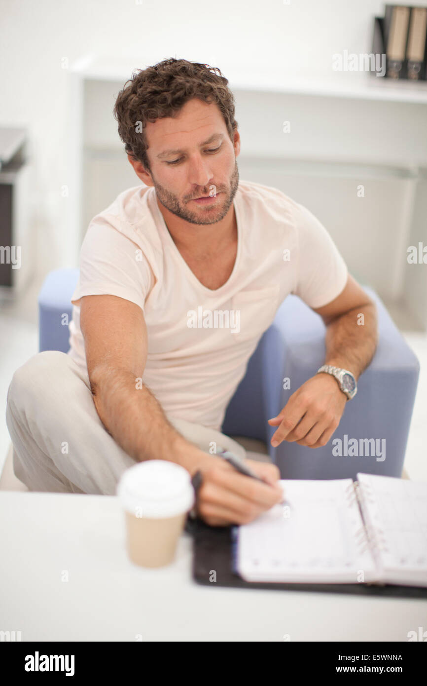 Mid adult man making notes - Stock Image