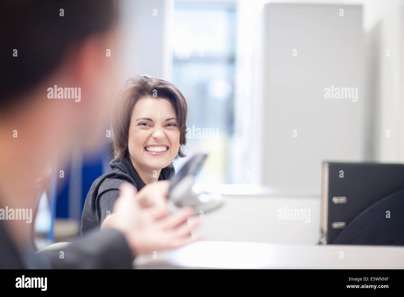 Female office worker laughing Stock Photo