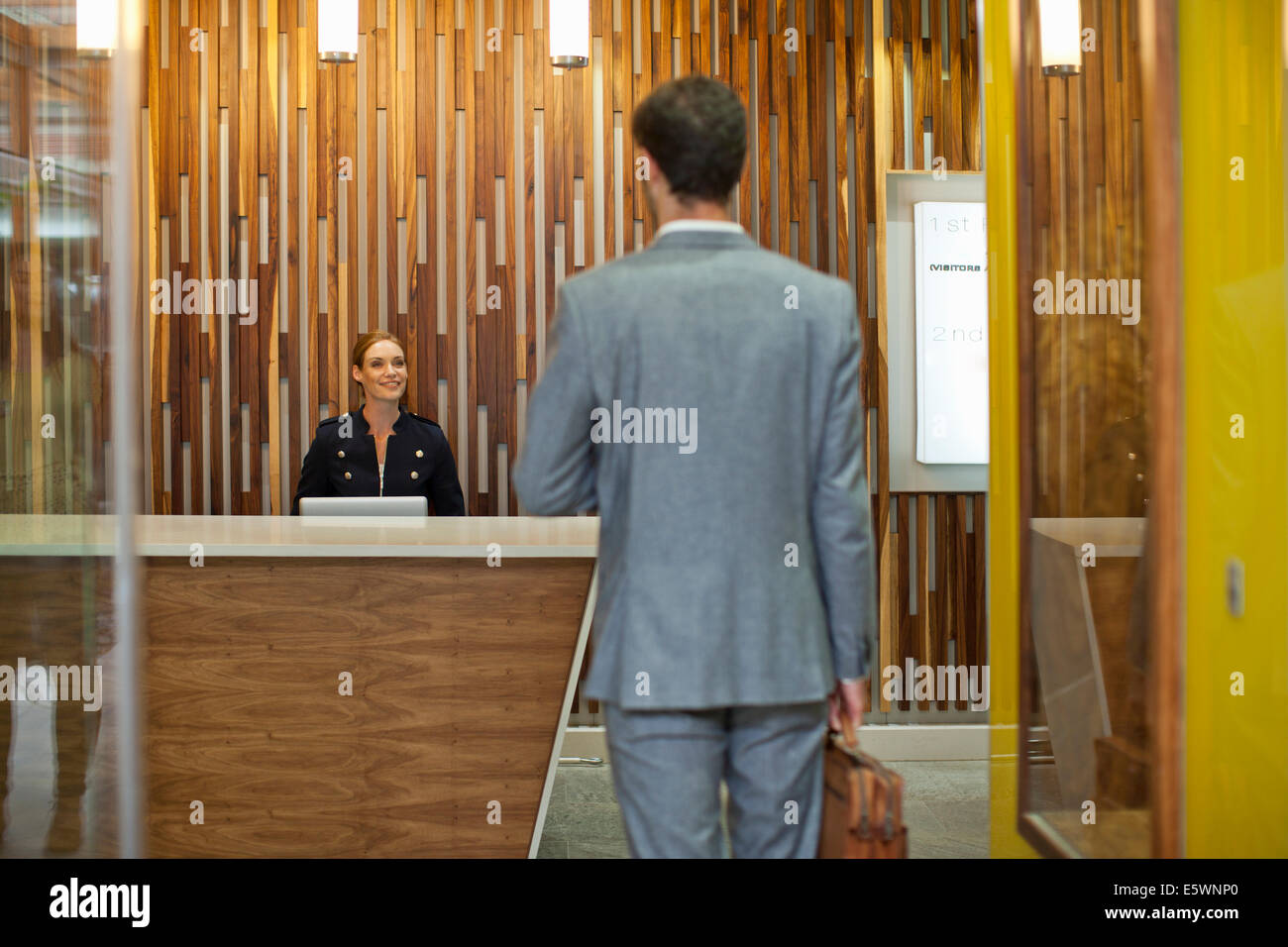 Businessman arriving at office reception - Stock Image