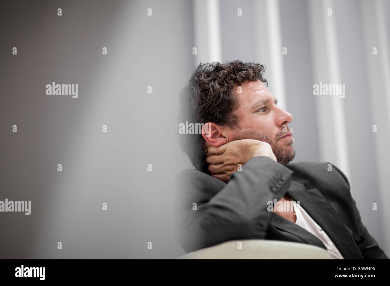 Businessman leaning on elbow - Stock Image
