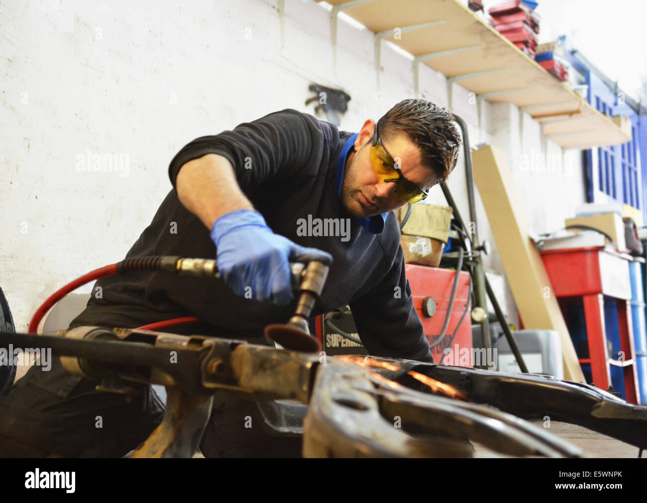 Mechanic cutting engine part with grinder - Stock Image