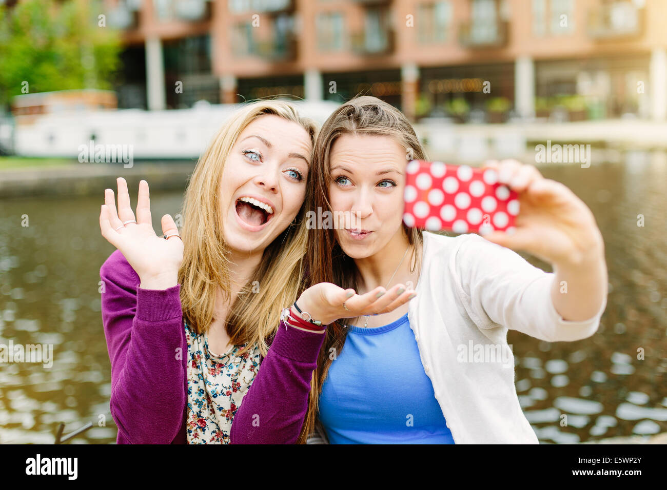 Friends taking selfie by canal - Stock Image