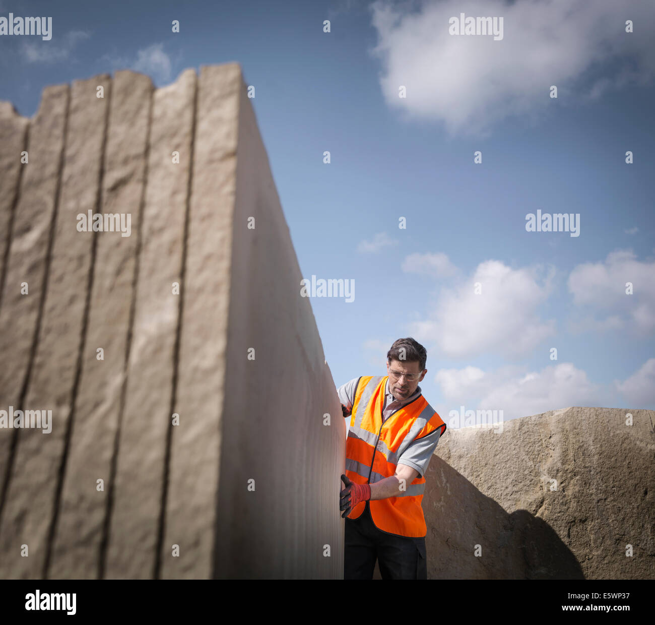 Quarry worker inspecting cut stone, low angle view - Stock Image