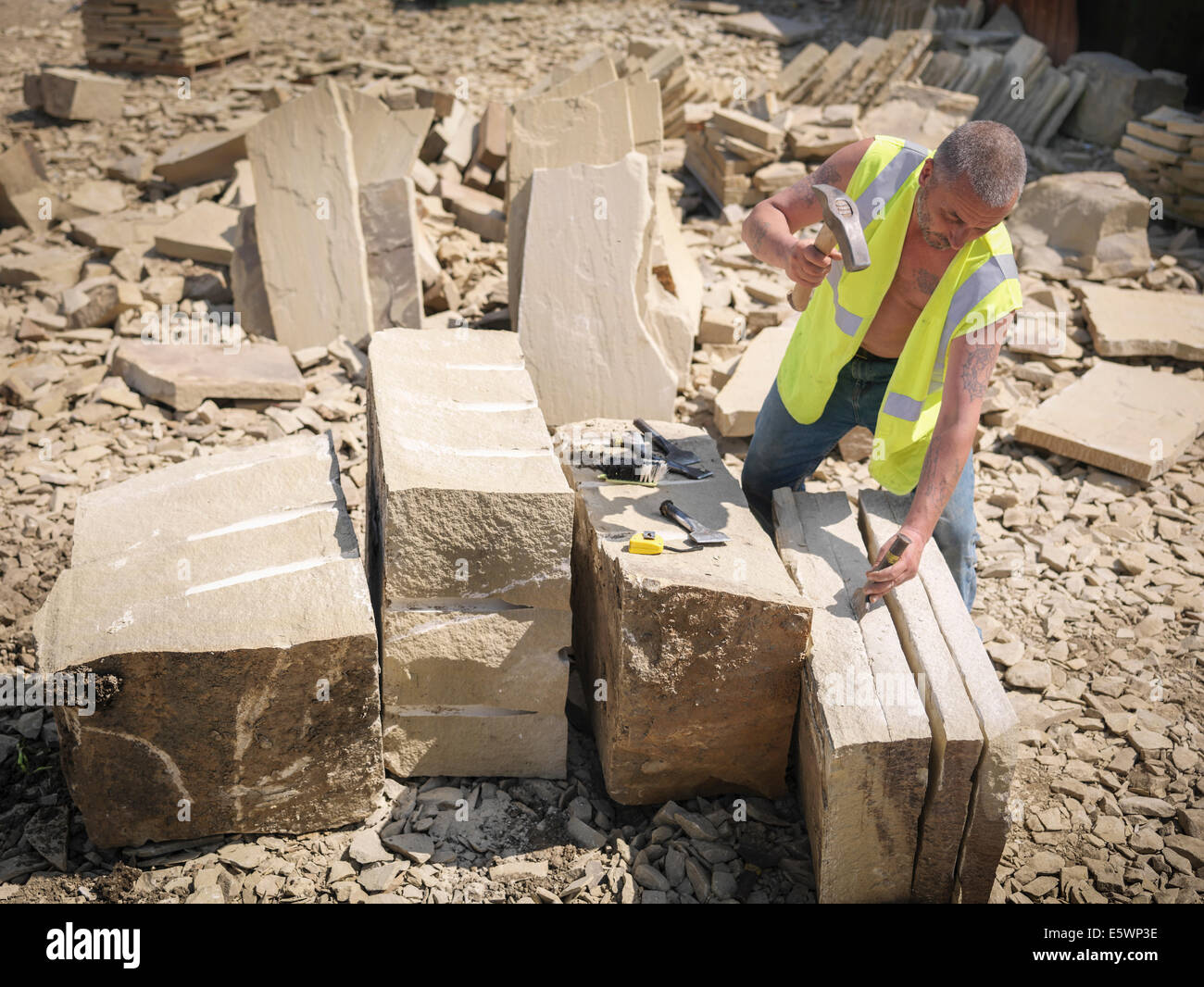 Quarry worker splitting sandstone in Yorkshire stone quarry, elevated view - Stock Image