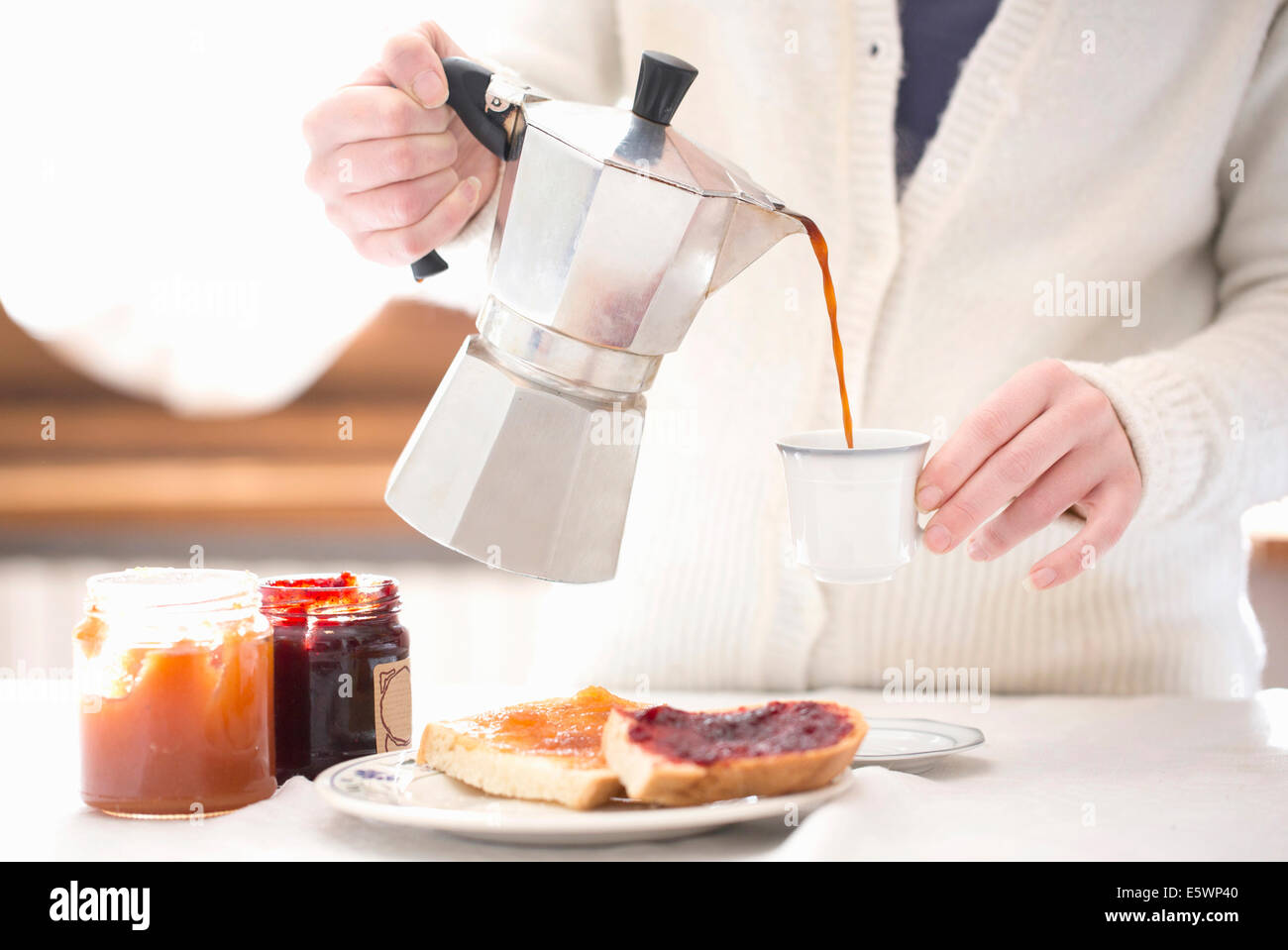 Cropped shot of young woman pouring coffee for breakfast Stock Photo