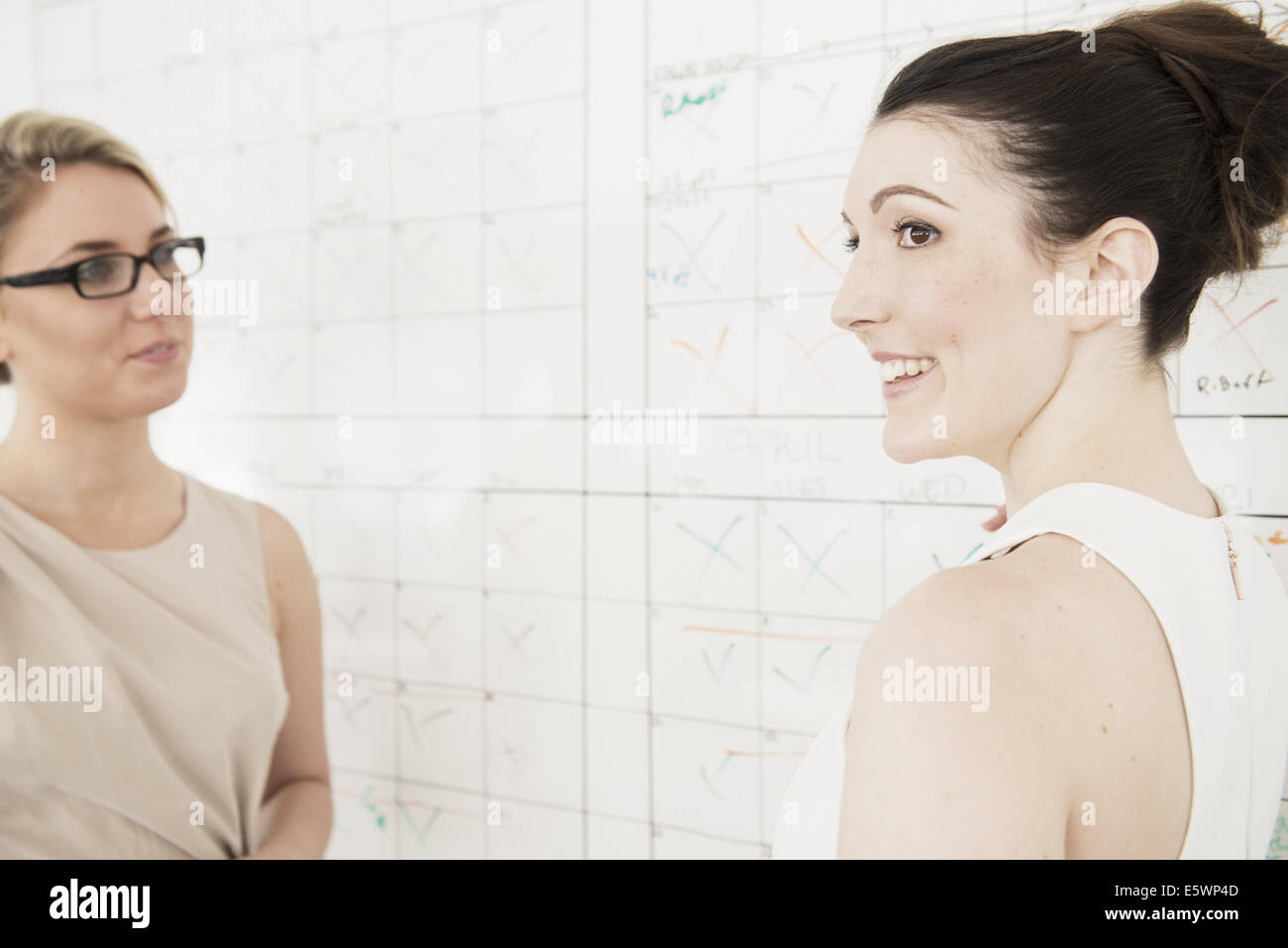 Two young businesswomen planning in office - Stock Image