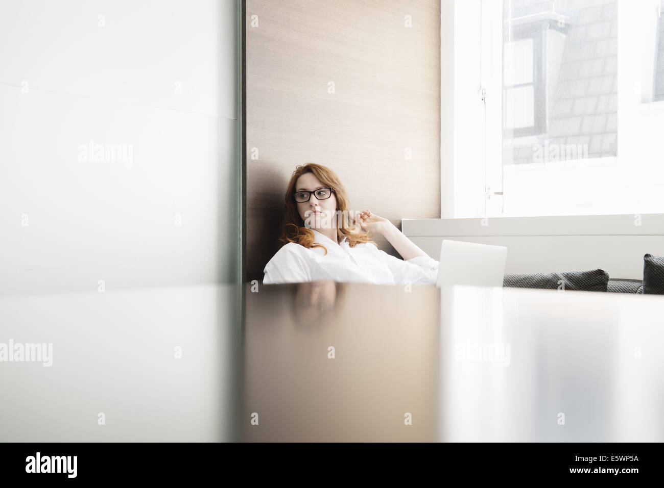 Mid adult businesswoman contemplating in new office - Stock Image