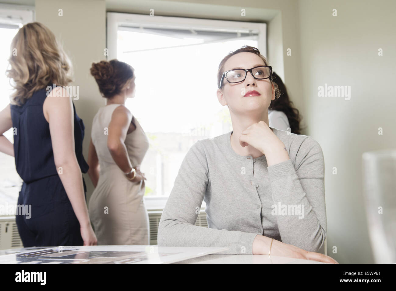 Young businesswoman gazing whilst colleagues look out of window - Stock Image