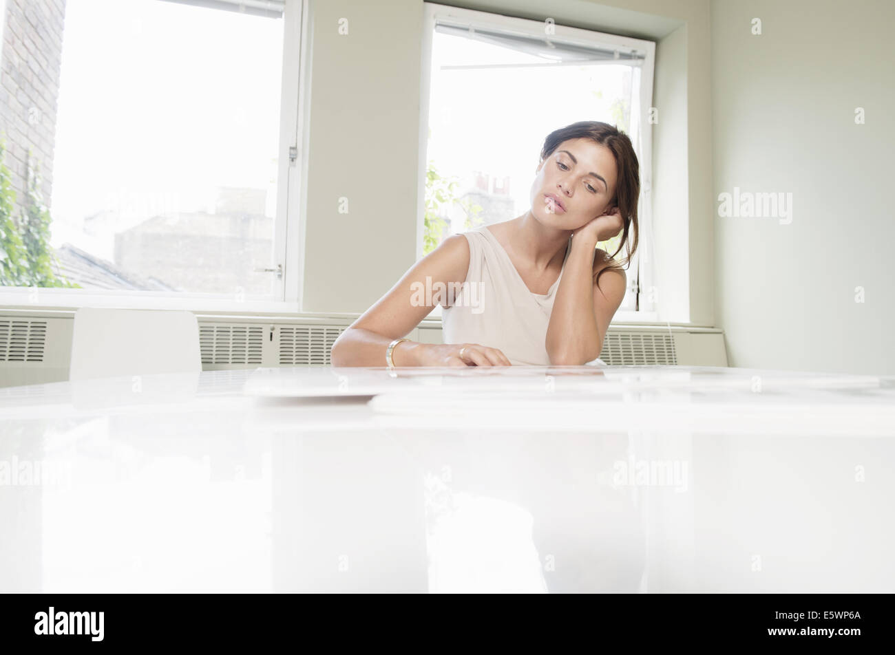 Young businesswoman looking stressed in office - Stock Image