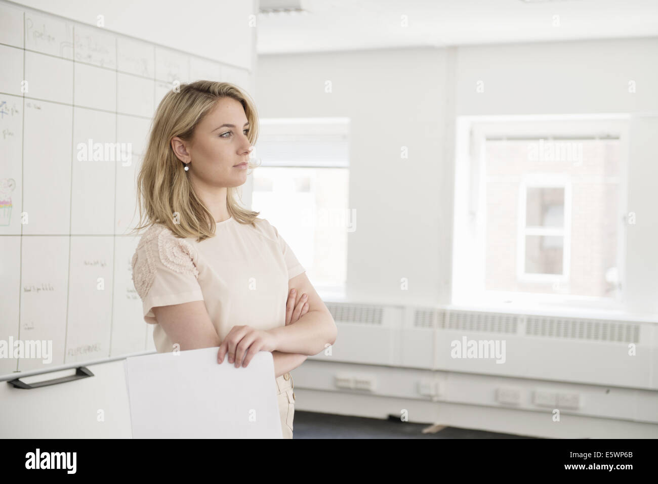 Young businesswoman contemplating in office - Stock Image