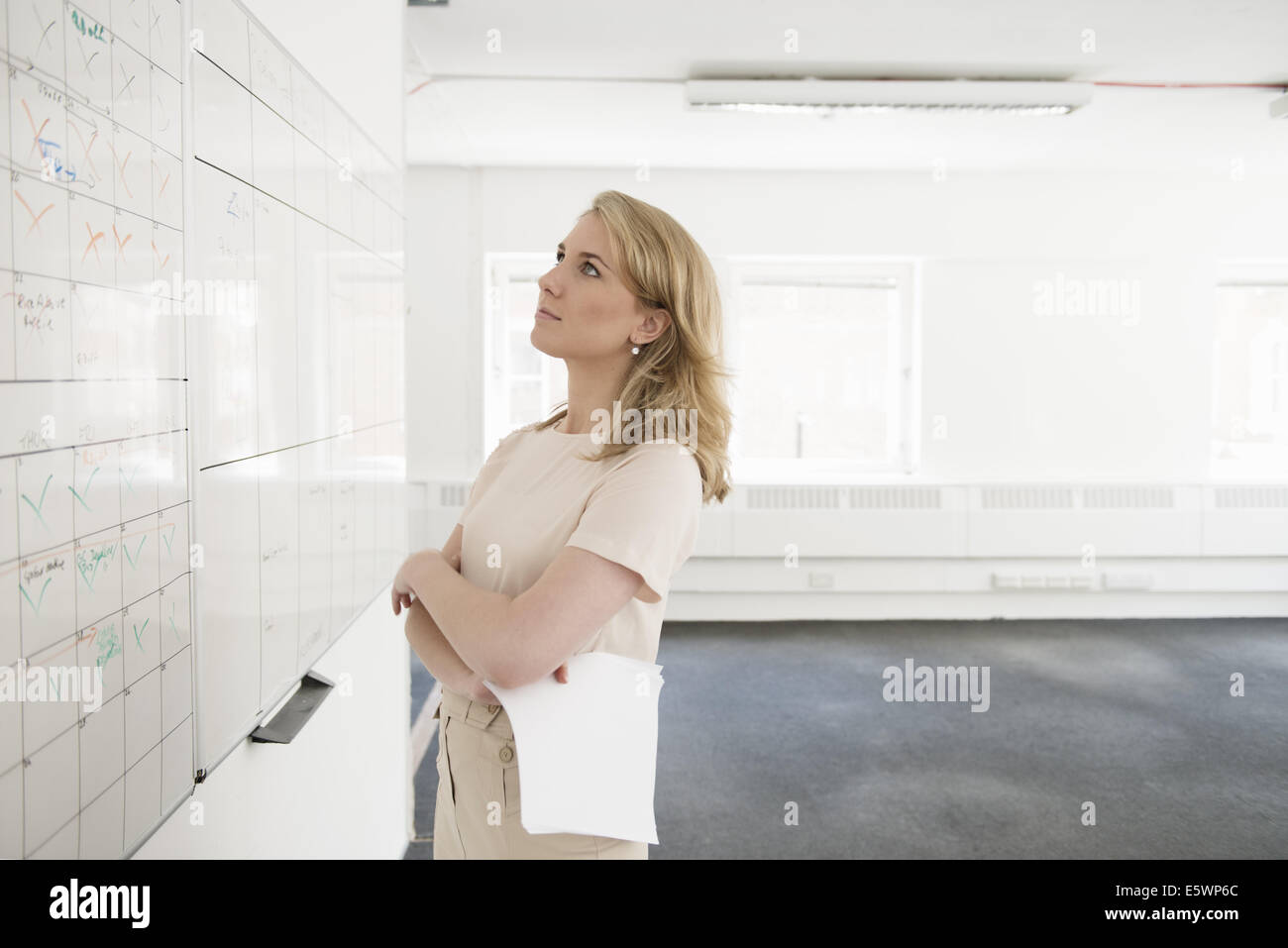 Young businesswoman contemplating whiteboard in empty office - Stock Image