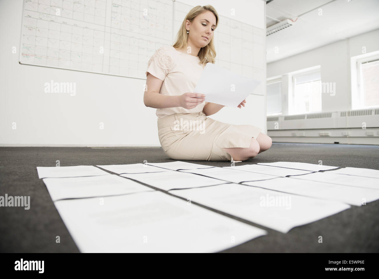 Young businesswoman organizing paperwork on office floor - Stock Image