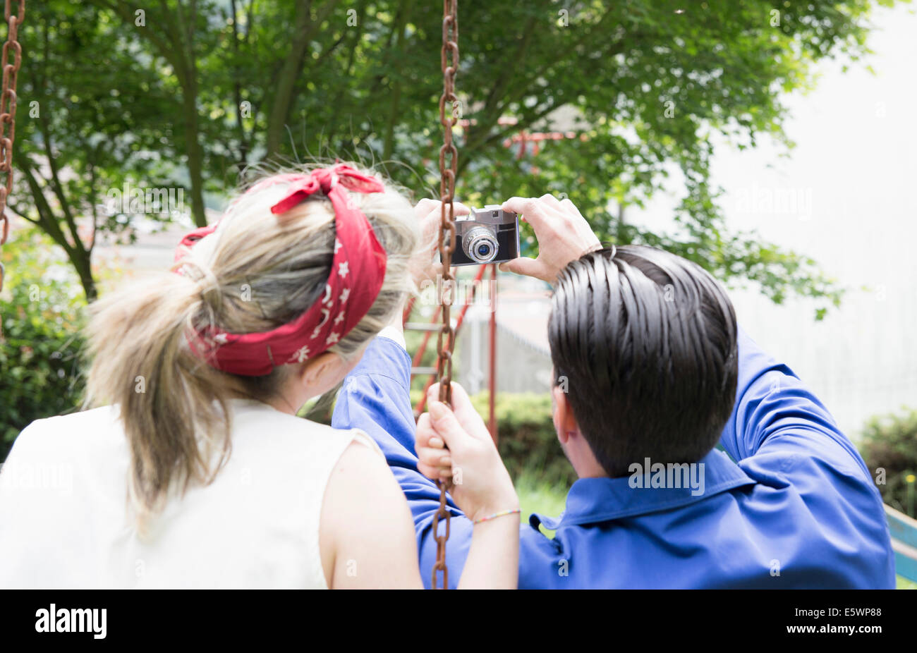 Rear view of young vintage couple taking selfie with camera in garden Stock Photo