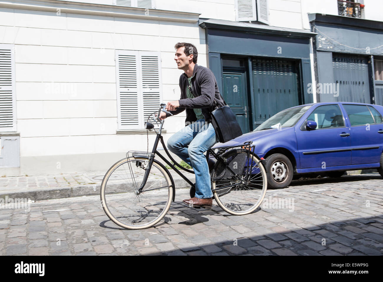 Mid adult man speeding down cobbled city street on bicycle - Stock Image