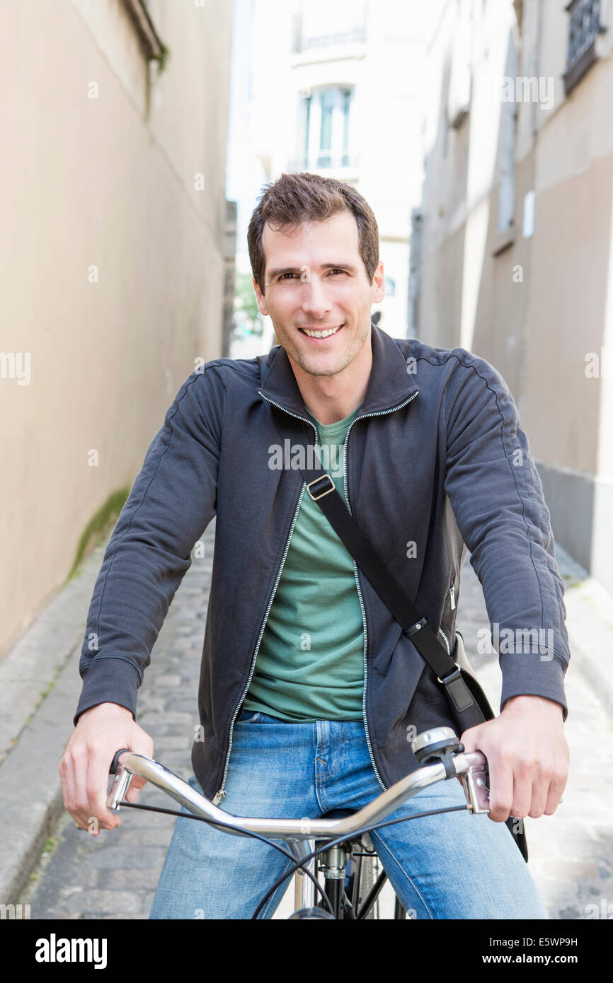 Portrait of mid adult man on bicycle in city street - Stock Image