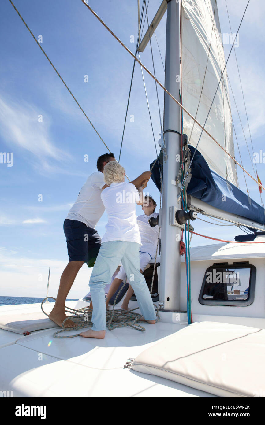 Father and brothers hauling sail on catamaran near Fuerteventura, Spain Stock Photo