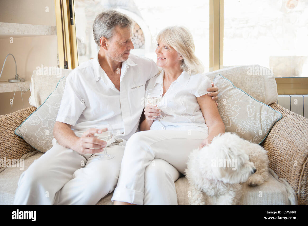Couple celebrating in hotel room - Stock Image
