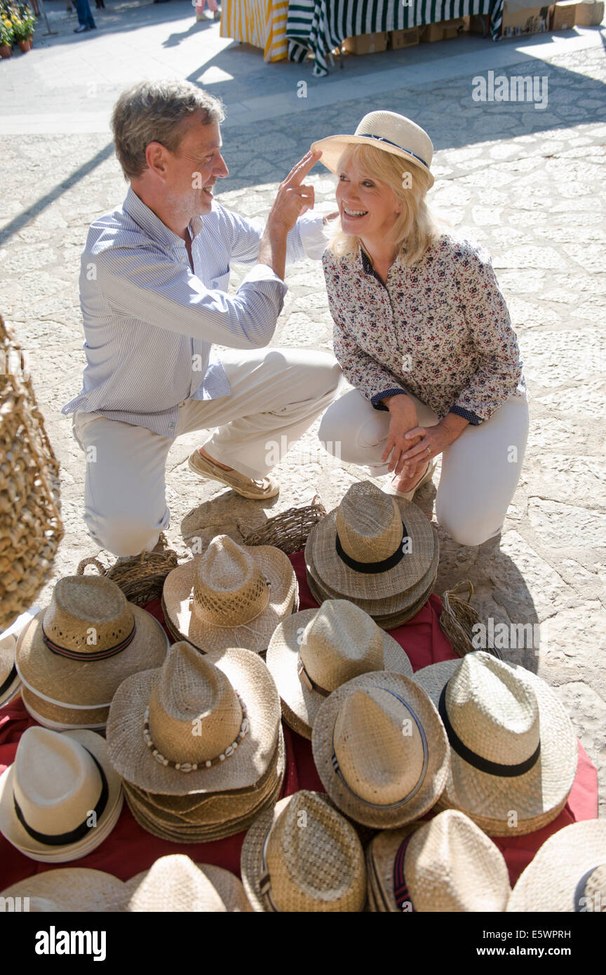 Couple shopping for hat at market, Mallorca, Spain - Stock Image