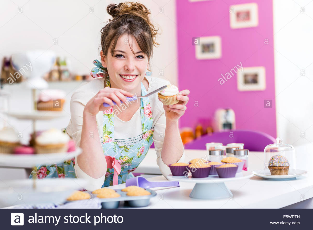 Woman decorating cupcake - Stock Image