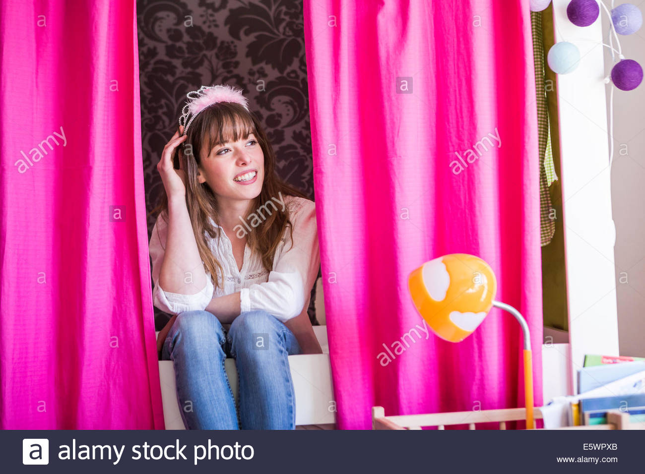 Woman with fluffy hairband sitting between pink curtains - Stock Image
