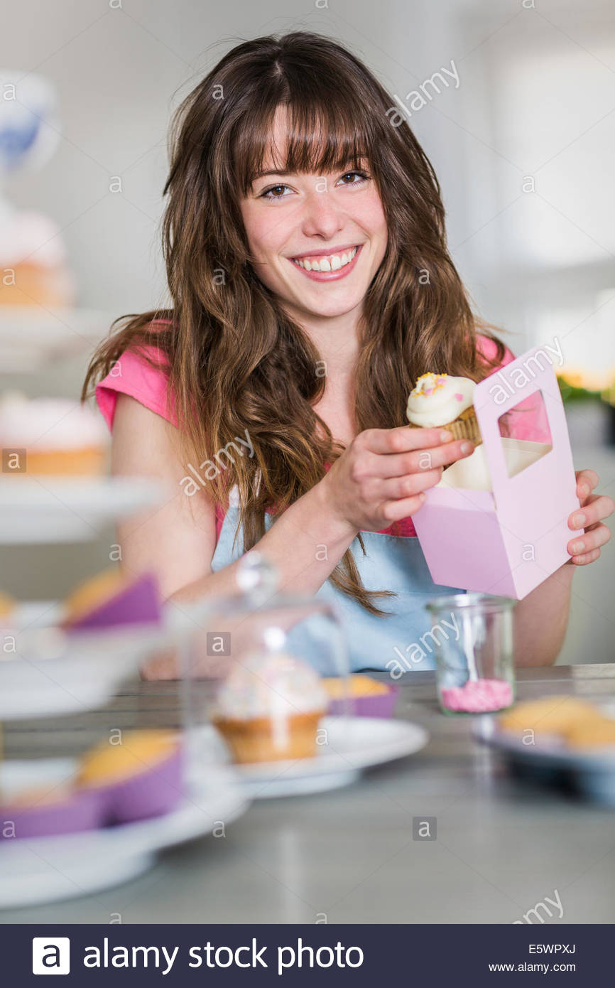 Woman packing homemade cupcakes - Stock Image
