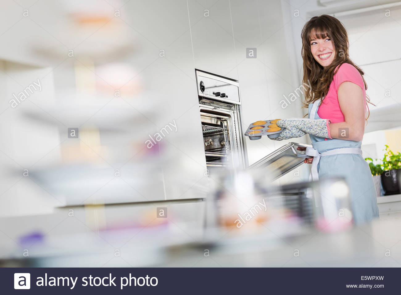 Woman removing cupcakes from oven - Stock Image
