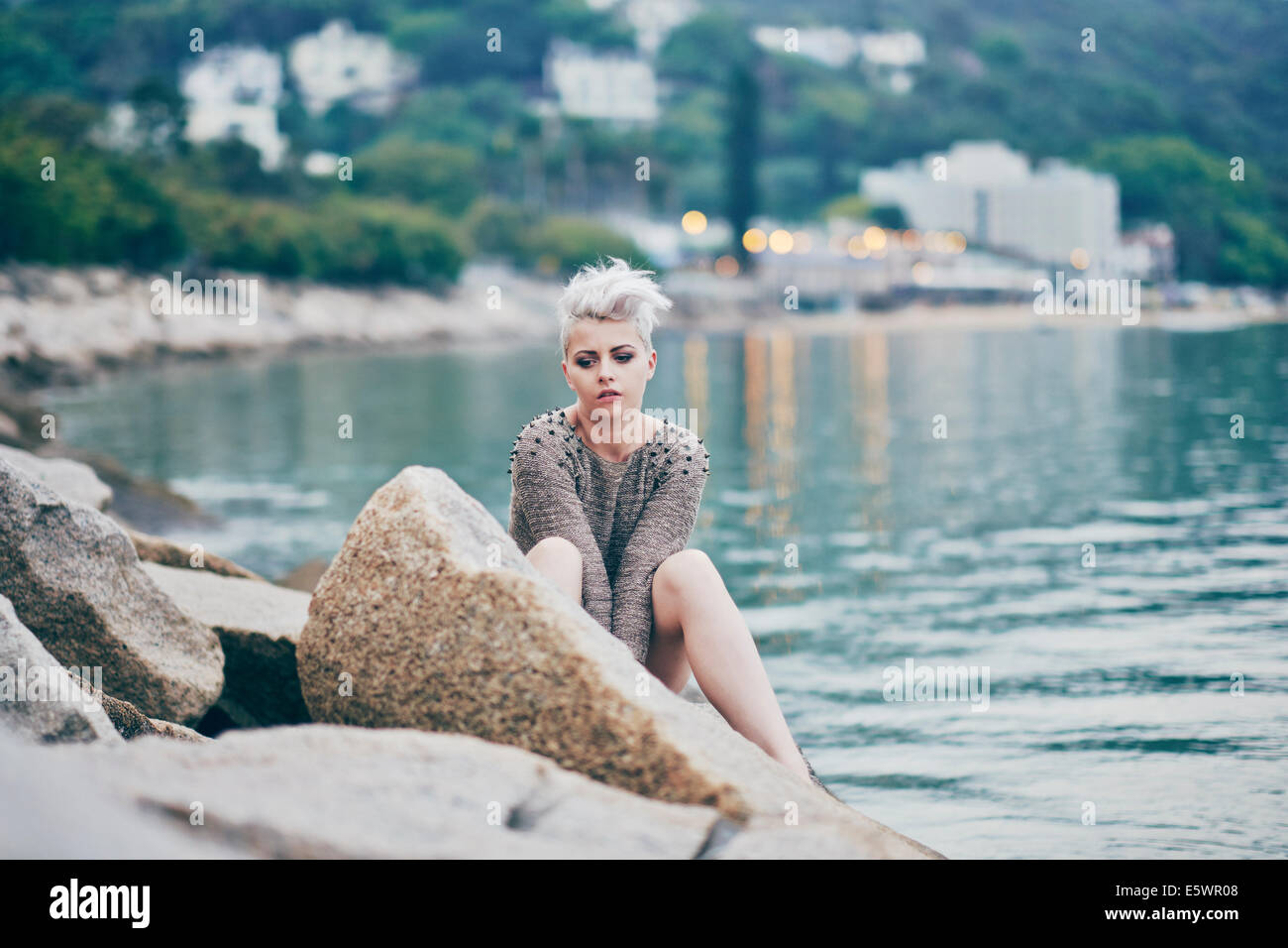 Young woman sitting alone on harbor rocks - Stock Image