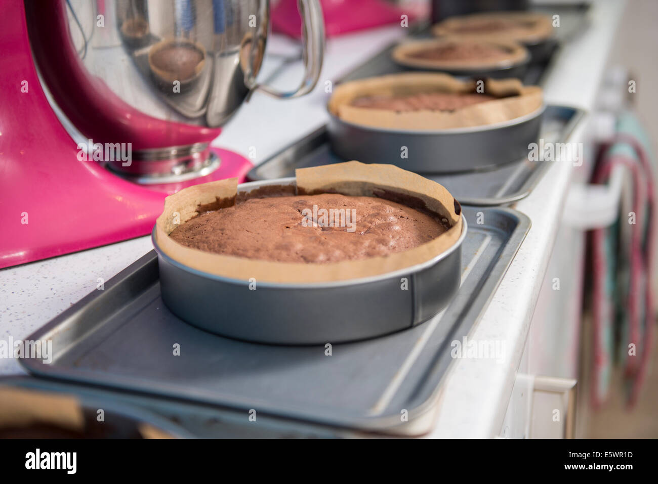 Row of cakes cooling off on top of ovens in bakery - Stock Image