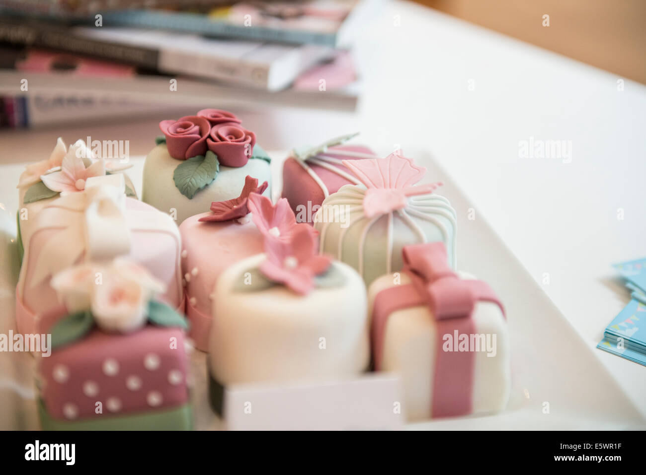 Close up of variety of individual decorated cakes in bakery - Stock Image