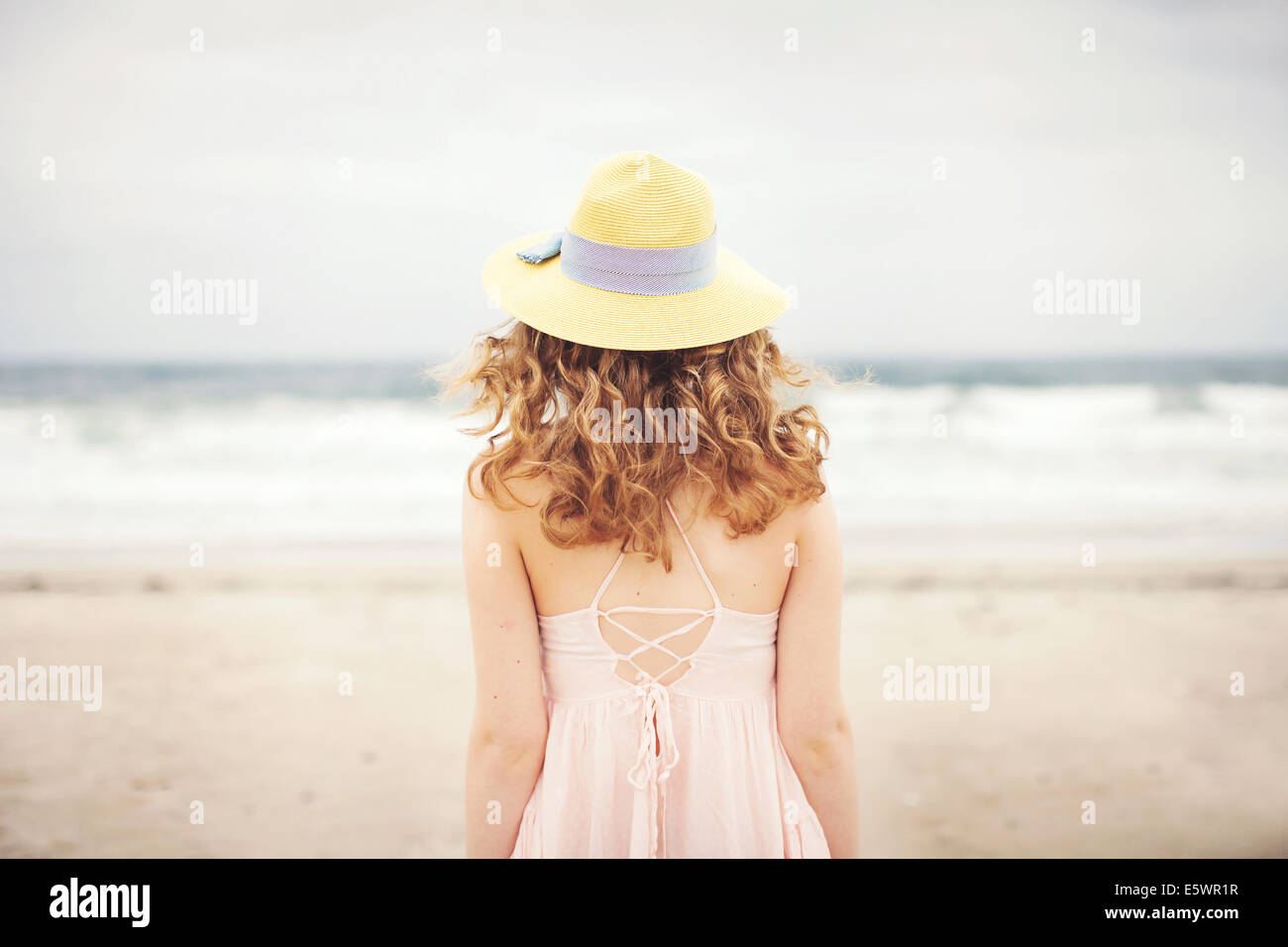 Rear view of teenage girl standing in front of sea, Hampton, New Hampshire, USA - Stock Image