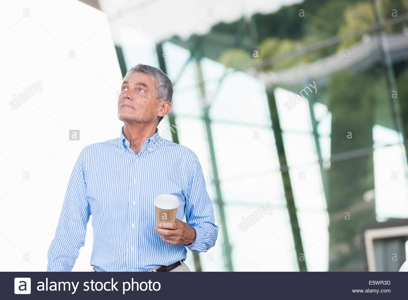 Senior adult businessman holding coffee - Stock Image