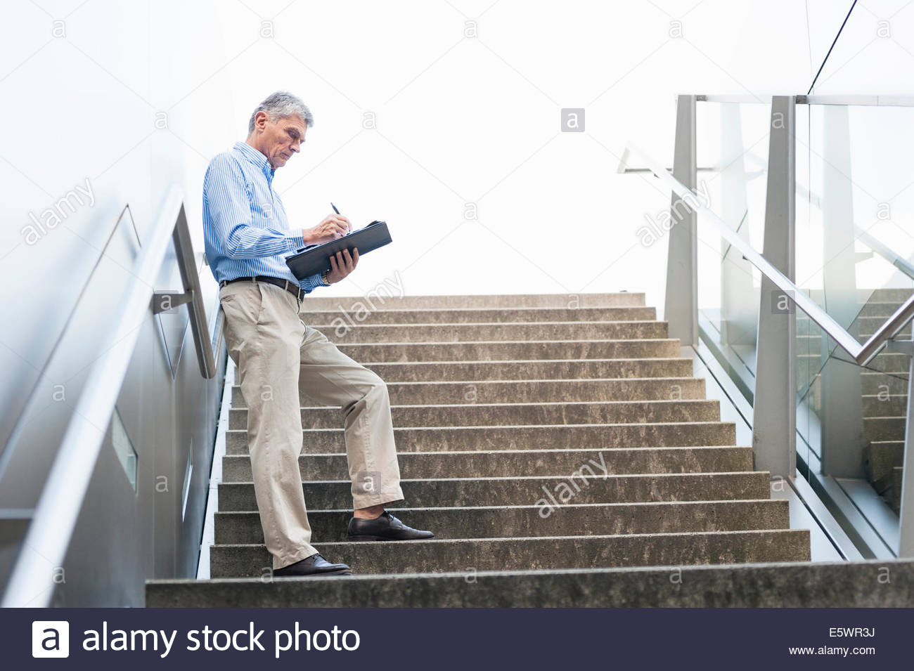 Senior adult businessman standing on stairs, holding notepad - Stock Image
