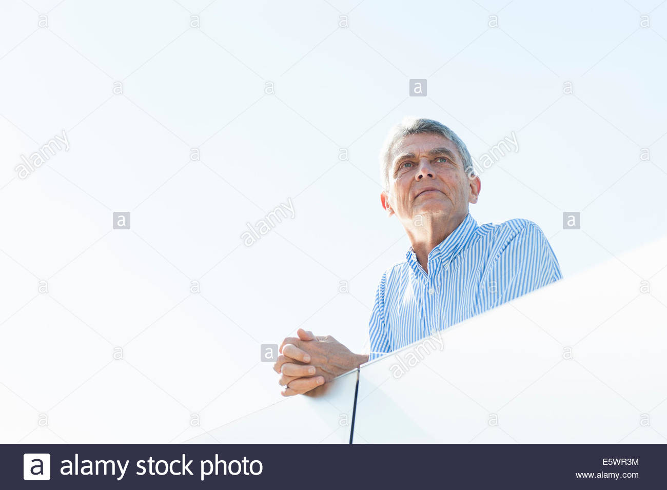 Senior adult businessman leaning on balcony - Stock Image