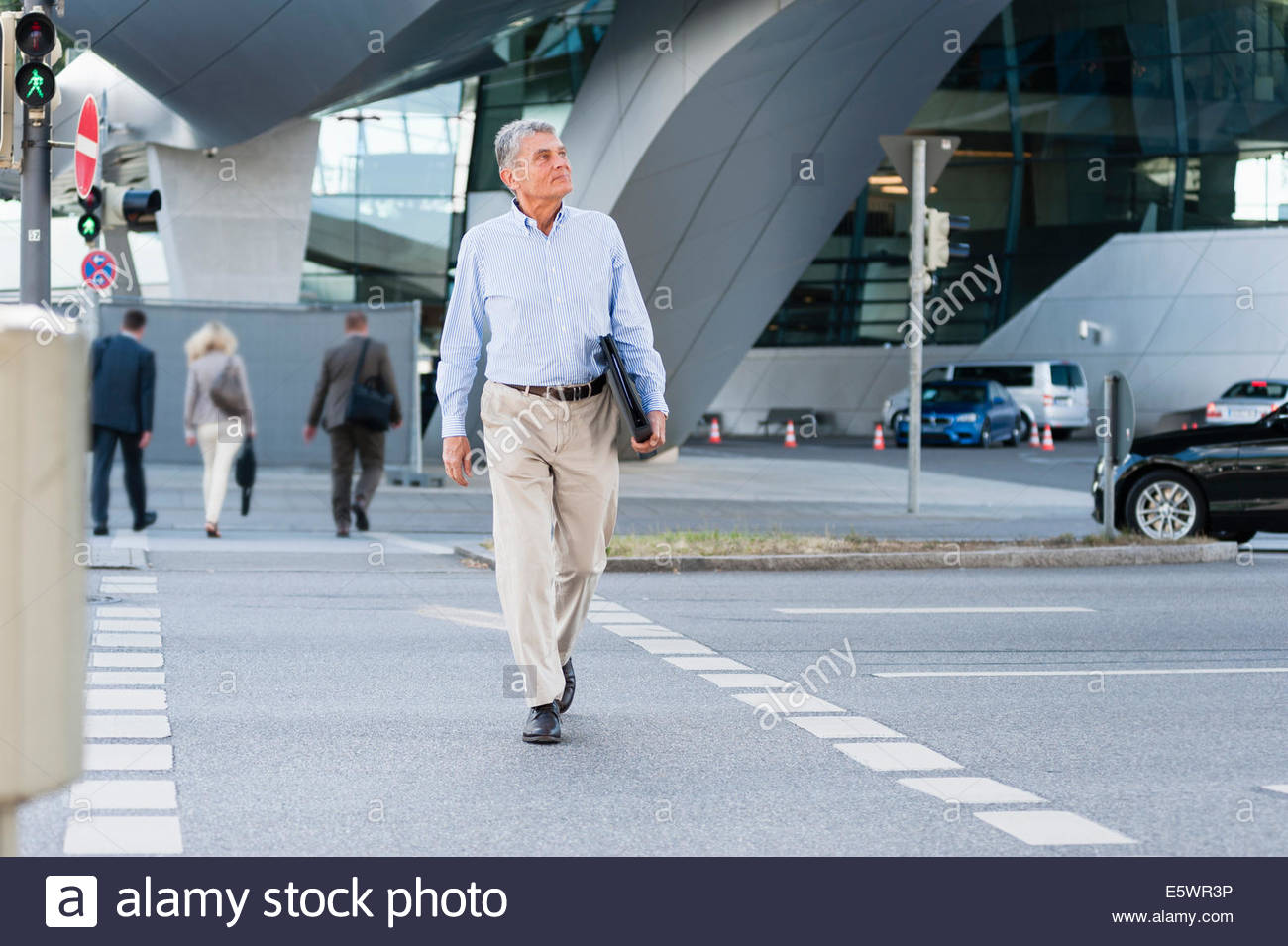 Senior adult businessman walking down street - Stock Image