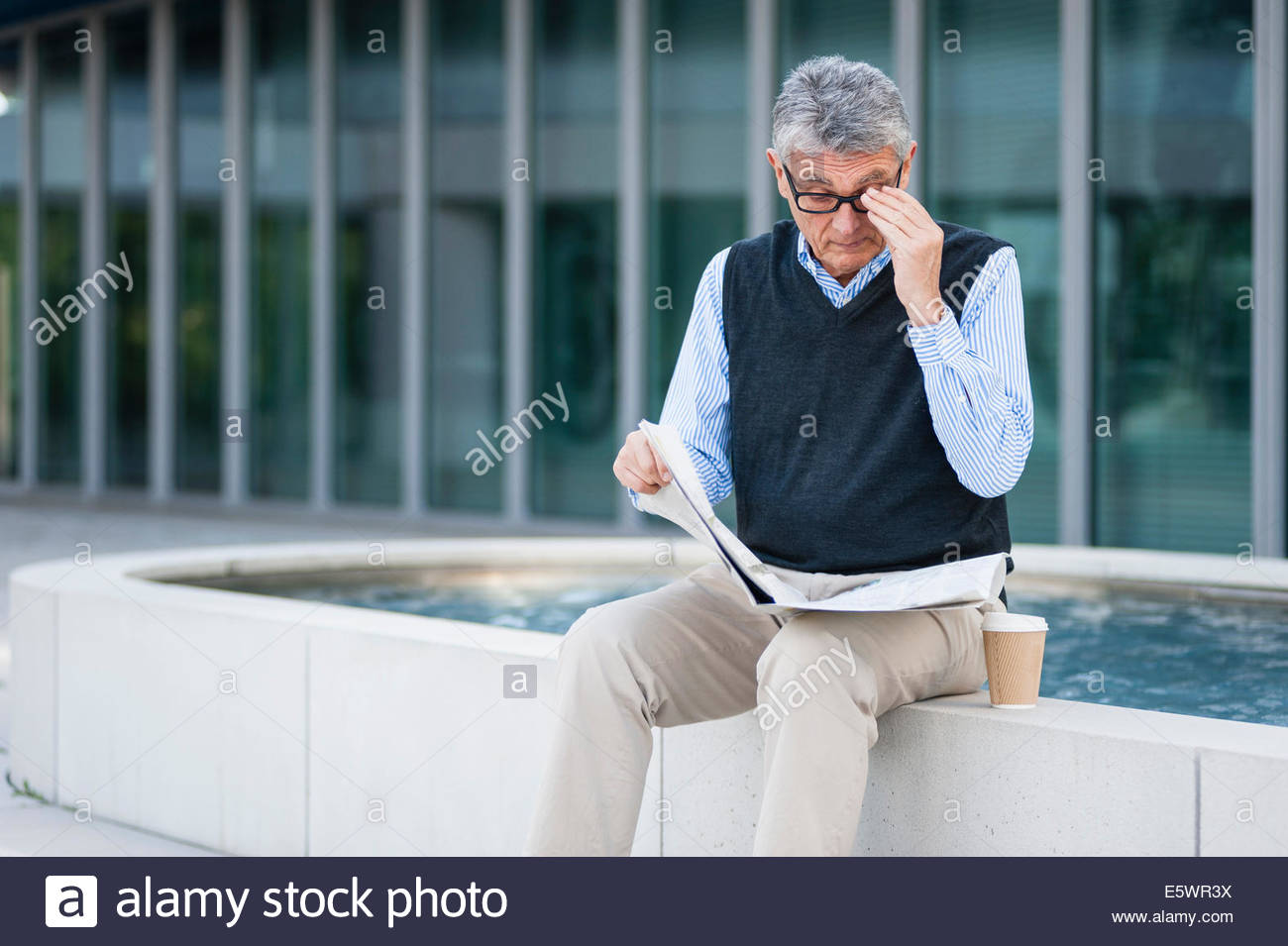 Senior adult businessman reading newspaper - Stock Image
