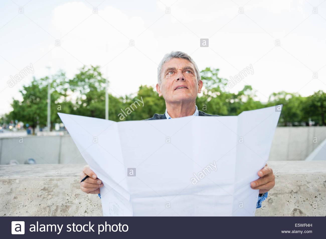 Senior adult businessman holding plans - Stock Image
