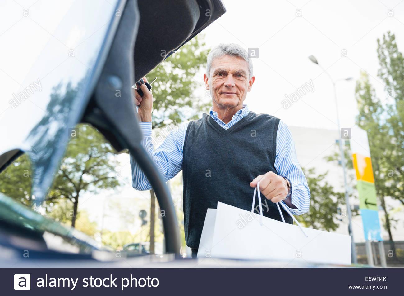 Senior adult businessman putting bag in car boot - Stock Image