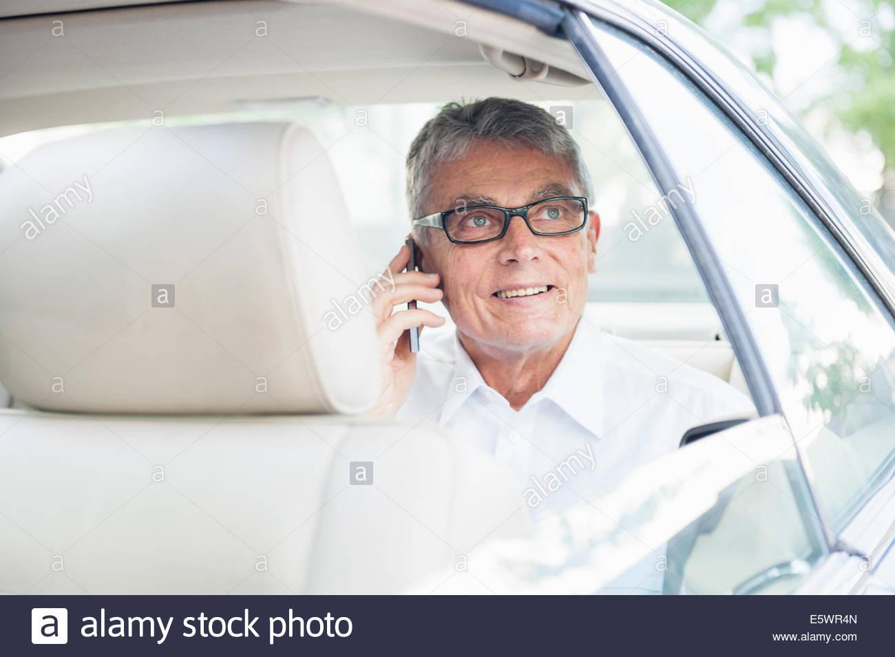 Senior adult businessman in car, using mobile phone - Stock Image