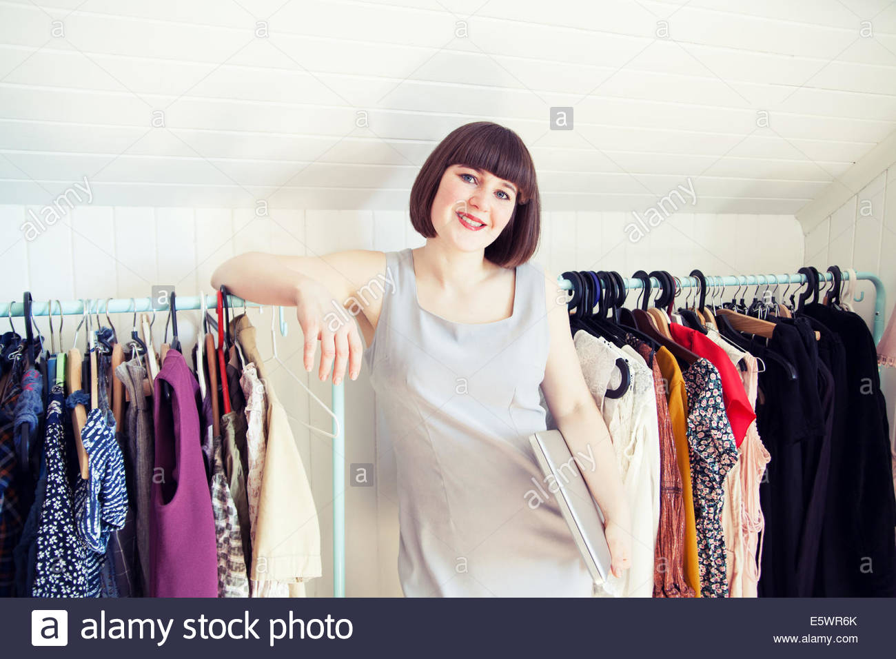 Portrait of young woman leaning on clothes rail in dressing room - Stock Image