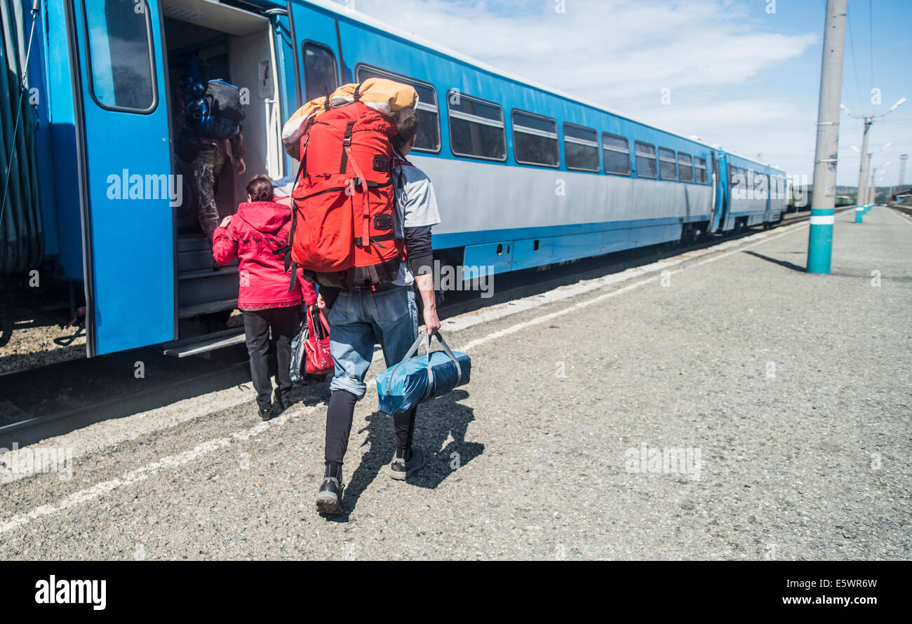 Rear view of young hikers with backpacks boarding a train - Stock Image
