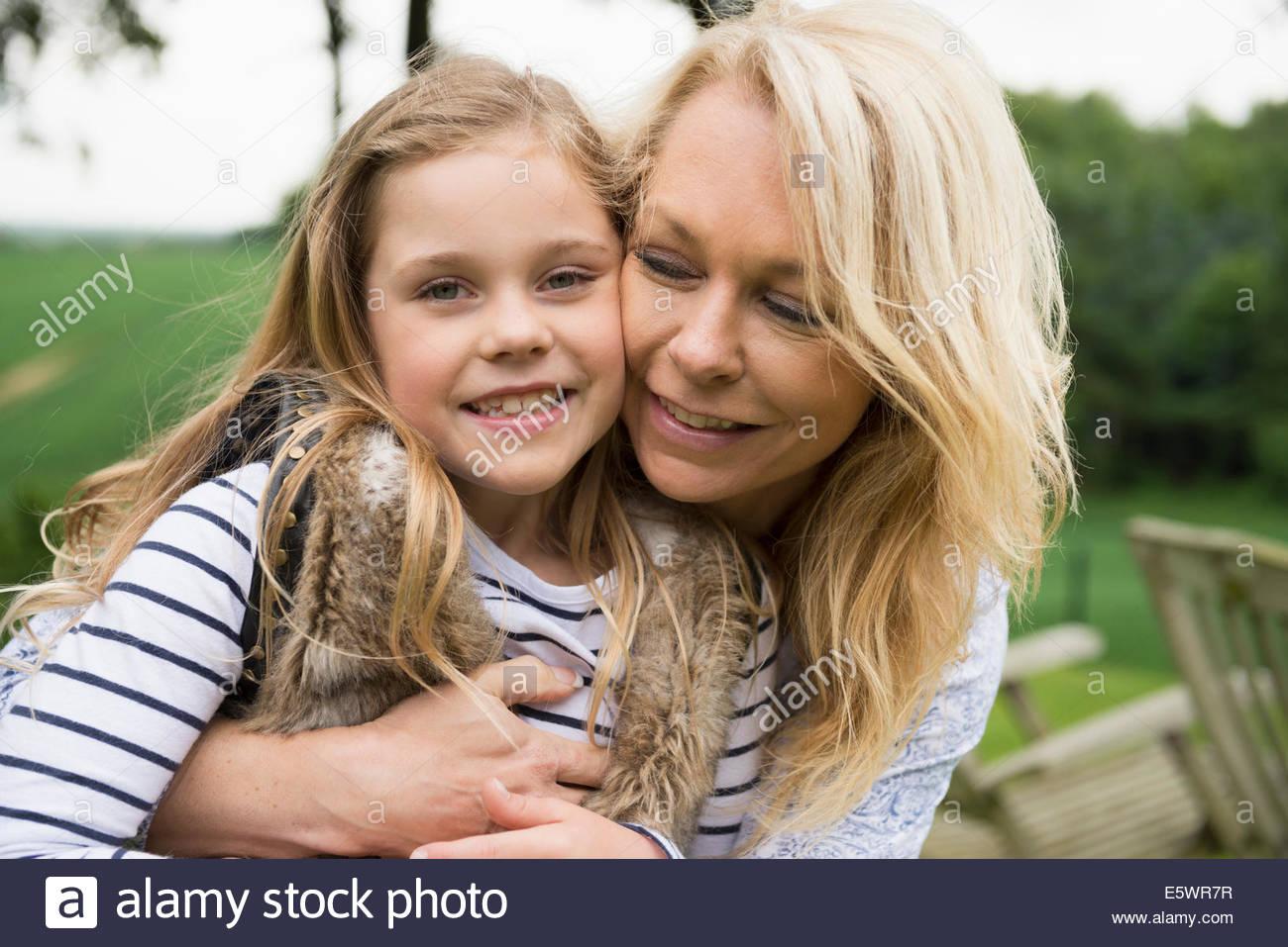 Mother hugging daughter, portrait - Stock Image