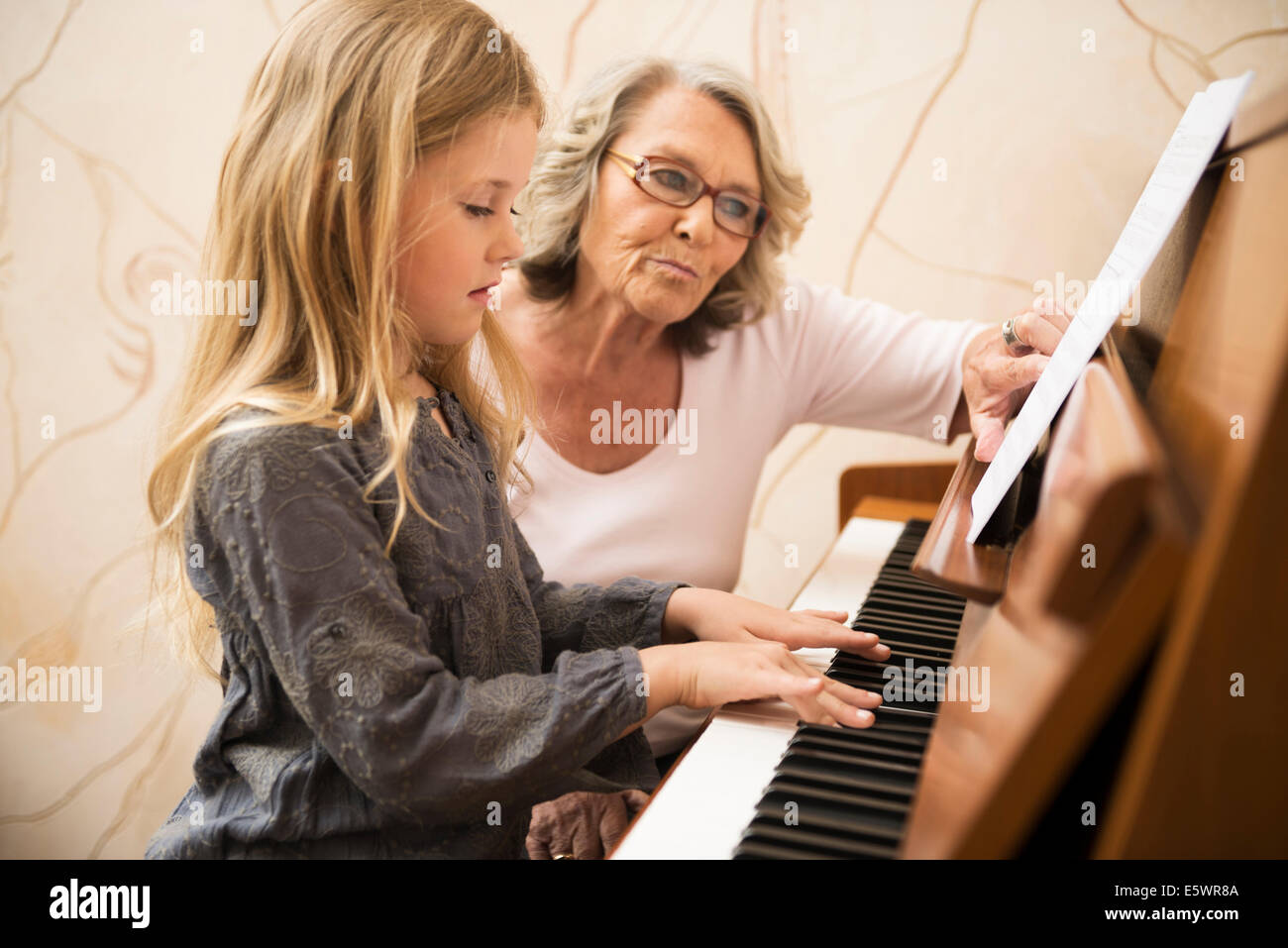 Grandmother teaching granddaughter piano - Stock Image
