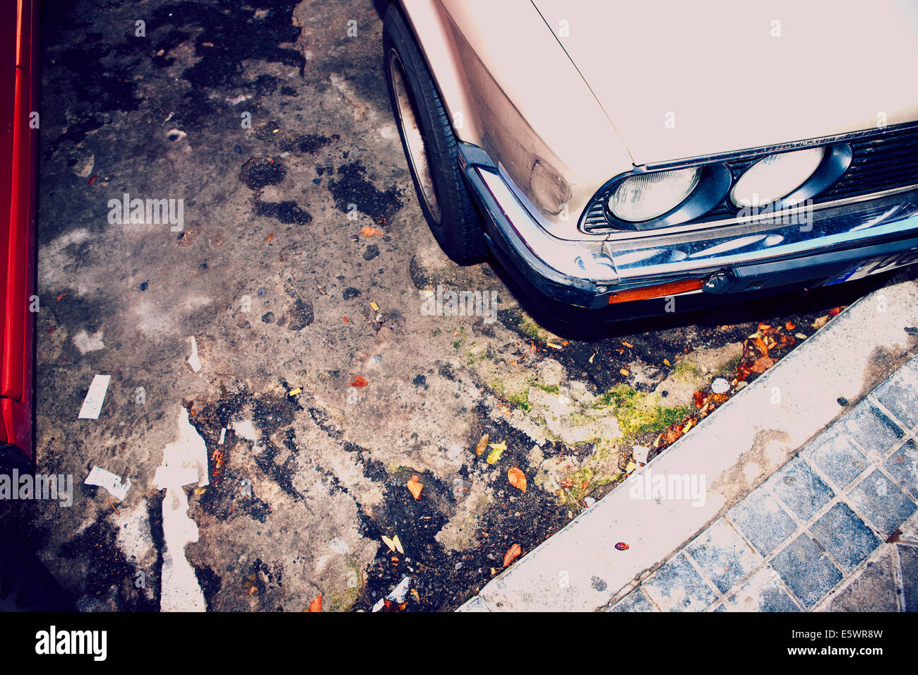 High angle cropped image of car parked next to kerb - Stock Image