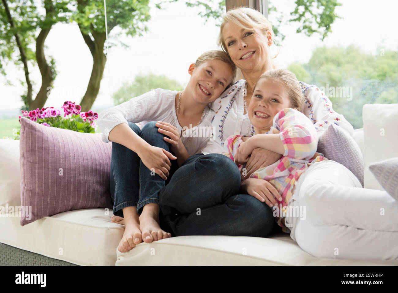 Mother and daughters sitting on sofa - Stock Image