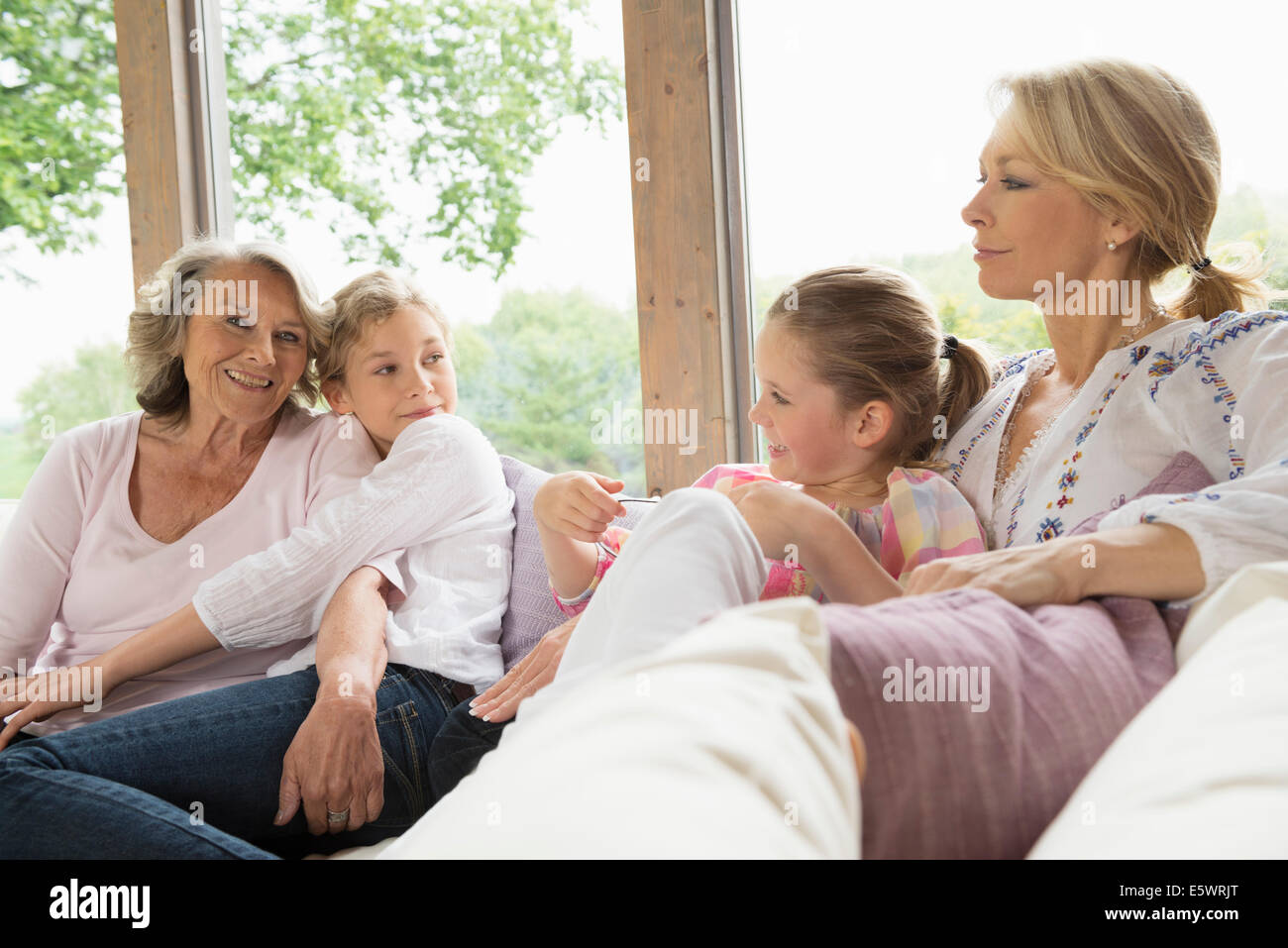 Grandmother, daughter and granddaughters on sofa - Stock Image