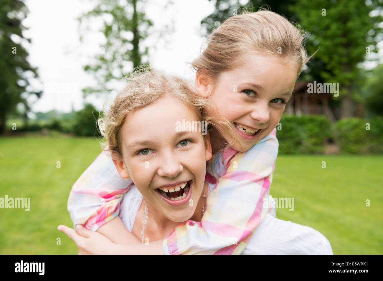 Two sisters hugging, portrait - Stock Image