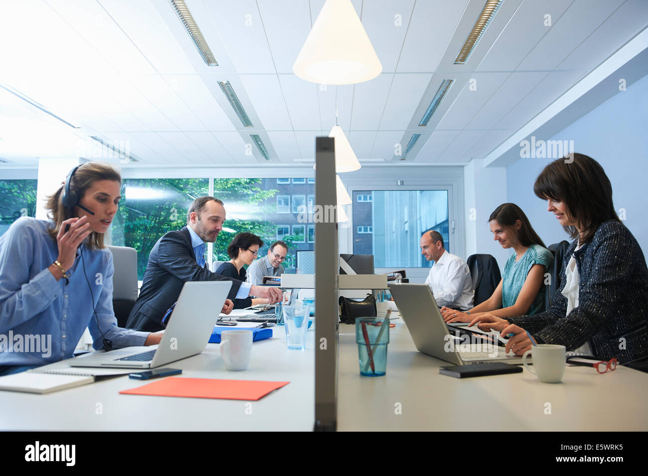 Businesspeople sitting on opposite sides of screen partition, working - Stock Image