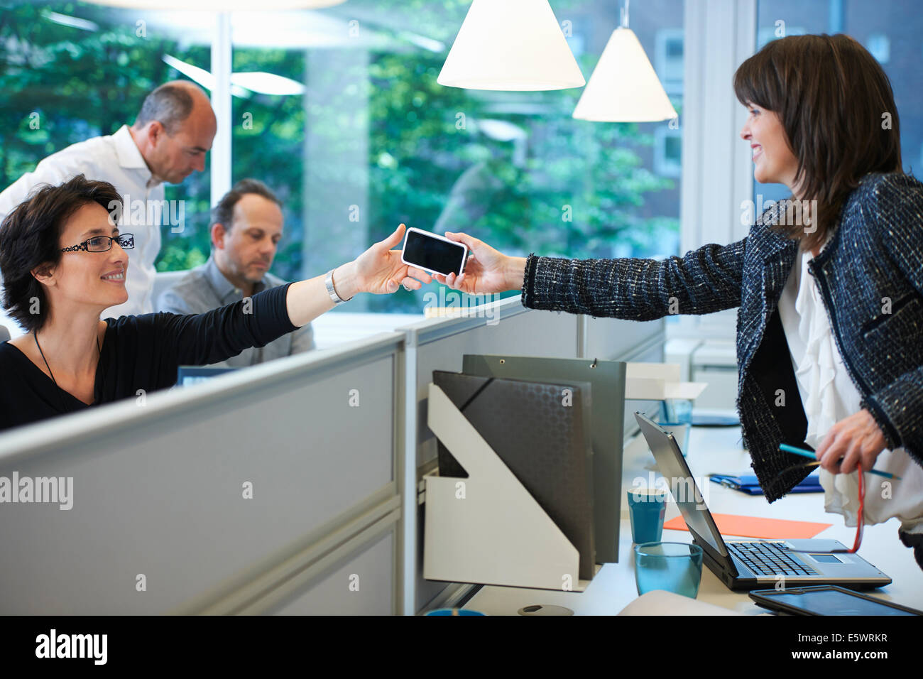 Woman passing smartphone to colleague - Stock Image