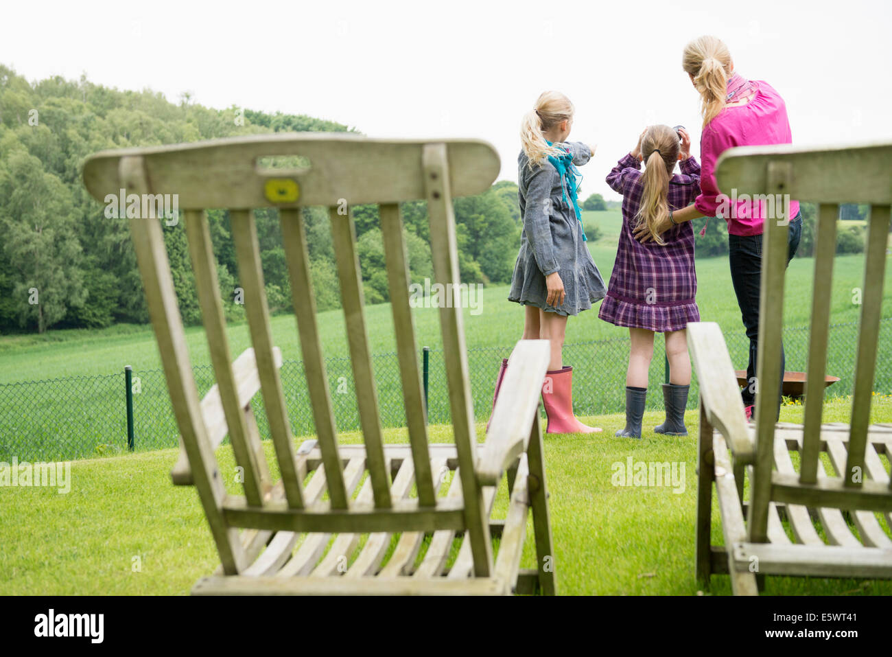 Mother and daughters using binoculars, chairs in foreground - Stock Image